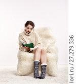 Купить «Brunette woman on furry arm-chair with book in hands», фото № 27279336, снято 8 октября 2017 г. (c) Serg Zastavkin / Фотобанк Лори