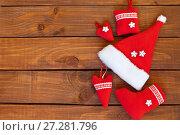 Купить «Традиционные красные новогодние сувениры ручной работы на деревянном фоне. Место для поздравительного текста», фото № 27281796, снято 10 декабря 2017 г. (c) Виктория Катьянова / Фотобанк Лори