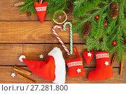Купить «Новый Год. Еловые ветки с шишками, красные игрушки ручной работы, конфеты и палочки корицы на деревянном фоне. Рождественский натюрморт», фото № 27281800, снято 10 декабря 2017 г. (c) Виктория Катьянова / Фотобанк Лори