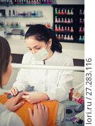 Купить «young manicurist filing and shaping nails in beauty salon», фото № 27283116, снято 28 апреля 2017 г. (c) Яков Филимонов / Фотобанк Лори