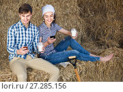 portrait of two farmers taking a pause in the hay and having their phones in hands. Стоковое фото, фотограф Яков Филимонов / Фотобанк Лори