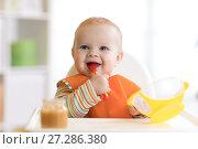 Купить «Happy infant baby boy spoon eats itself», фото № 27286380, снято 24 ноября 2017 г. (c) Оксана Кузьмина / Фотобанк Лори