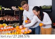 Купить «Young loving couple deciding on fruits in shop», фото № 27288576, снято 23 ноября 2016 г. (c) Яков Филимонов / Фотобанк Лори