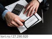 Купить «Предприниматель рассматривает налоговую декларацию на вменённый доход через лупу», эксклюзивное фото № 27290920, снято 6 ноября 2017 г. (c) Игорь Низов / Фотобанк Лори