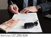 Купить «Покупка машины. Российские деньги и автомобильный ключ от зажигания  на фоне мужчины подписывающего  договор купли продажи. Фокус на руках», эксклюзивное фото № 27290924, снято 6 ноября 2017 г. (c) Игорь Низов / Фотобанк Лори