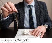 Купить «Покупка квартиры. Мужчина держит в руке ключи от дома на фоне документов и денег. Фокус на ключах», эксклюзивное фото № 27290932, снято 6 ноября 2017 г. (c) Игорь Низов / Фотобанк Лори