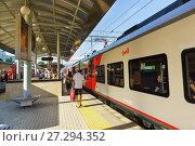 Купить «Пассажиры идут по платформе мимо пригородных поездов на железнодорожной станции Сочи», фото № 27294352, снято 9 июня 2017 г. (c) Наталья Гармашева / Фотобанк Лори