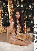 Купить «Christmas. Beautiful smiling girl in golden dress with glass of champagne on party over gift. Healthy long hair style. Makeup. Young attractive woman over xmas tree lights background. Happy New Year.», фото № 27294516, снято 29 ноября 2017 г. (c) Photobeauty / Фотобанк Лори