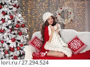 Купить «Christmas. Beautiful santa girl. Smiling woman with long hair sitting on cozy sofa holding white knitted chunky yarn blanket in home over xmas snowflakes tree lights background. Happy New Year!», фото № 27294524, снято 29 ноября 2017 г. (c) Photobeauty / Фотобанк Лори