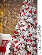 Купить «Snowy Christmas tree with red gifts decoration before bokeh lights on the wall in holiday room interior home», фото № 27294540, снято 24 февраля 2020 г. (c) Photobeauty / Фотобанк Лори