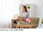 Купить «smiling woman opening parcel box at home», фото № 27296048, снято 22 апреля 2017 г. (c) Syda Productions / Фотобанк Лори