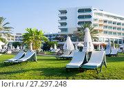 Купить «Paphos, Cyprus - July 20, 2017: Palm beach with empty sunbeds against Constantinou Bros Athena Beach Hotel. The hotel was fully refurbished in the winter of 10/11», фото № 27297248, снято 20 июля 2017 г. (c) Papoyan Irina / Фотобанк Лори
