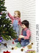 Купить «Little 5 years brother and 1 year sister in red plaid shirts and denim overalls decorate Christmas tree», фото № 27298200, снято 16 декабря 2017 г. (c) ivolodina / Фотобанк Лори