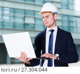 Smiling builder in suit and hat with folder is exploring project in his laptop. Стоковое фото, фотограф Яков Филимонов / Фотобанк Лори