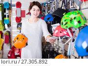 Купить «Woman examines helmet models», фото № 27305892, снято 24 февраля 2017 г. (c) Яков Филимонов / Фотобанк Лори