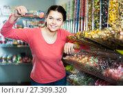 Купить «Girl studying assortment of marmalade and bonbons», фото № 27309320, снято 22 марта 2017 г. (c) Яков Филимонов / Фотобанк Лори