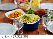 Купить «pasta with basil in bowl and other food on table», фото № 27322508, снято 5 октября 2017 г. (c) Syda Productions / Фотобанк Лори