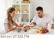 Купить «couple with smartphones having breakfast at home», фото № 27322716, снято 19 октября 2017 г. (c) Syda Productions / Фотобанк Лори