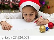 Купить «Симпатичная маленькая девочка в красном колпаке пишет письмо Деду Морозу», фото № 27324008, снято 19 декабря 2017 г. (c) Лариса Капусткина / Фотобанк Лори
