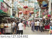 Купить «People walk on Petaling Street in Chinatown, Kuala Lumpur, Malaysia.», фото № 27324692, снято 10 апреля 2015 г. (c) age Fotostock / Фотобанк Лори