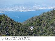 Большая гондола начинает подниматься по тросу от станции Kayatani на вершину горы Misen. Вид на залив и город Хиросима. Остров Itsukusima, Япония (2013 год). Стоковое фото, фотограф Кекяляйнен Андрей / Фотобанк Лори