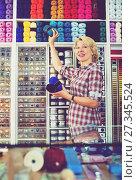 Купить «Seller picking yarn and wool balls», фото № 27345524, снято 23 сентября 2018 г. (c) Яков Филимонов / Фотобанк Лори