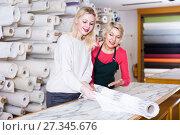 Купить «Female seller 55-60 years old is showing fabrics to young woman 25-30 years old», фото № 27345676, снято 15 февраля 2017 г. (c) Яков Филимонов / Фотобанк Лори