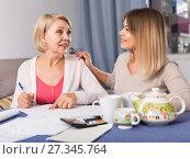 Купить «Daughter helps mother to lead home accounting», фото № 27345764, снято 13 ноября 2017 г. (c) Яков Филимонов / Фотобанк Лори