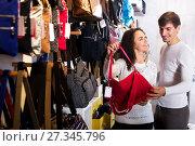 Купить «Female shopgirl helping young man to select handbag», фото № 27345796, снято 16 октября 2018 г. (c) Яков Филимонов / Фотобанк Лори