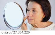 Купить «Elderly woman stroking the skin on the face», видеоролик № 27354220, снято 5 января 2018 г. (c) Илья Шаматура / Фотобанк Лори