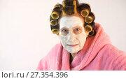 Купить «Evil wife with a cosmetic mask and curlers», видеоролик № 27354396, снято 5 января 2018 г. (c) Илья Шаматура / Фотобанк Лори
