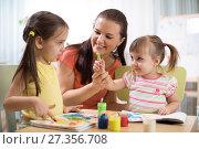 Купить «Kids with young teacher woman painting on table together in kindergarten .», фото № 27356708, снято 29 ноября 2017 г. (c) Оксана Кузьмина / Фотобанк Лори