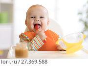 Купить «Happy infant baby boy spoon eats itself», фото № 27369588, снято 24 ноября 2017 г. (c) Оксана Кузьмина / Фотобанк Лори
