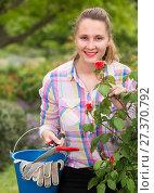 Купить «young woman with long curly hair smells roses flower outdoor», фото № 27370792, снято 18 апреля 2017 г. (c) Яков Филимонов / Фотобанк Лори
