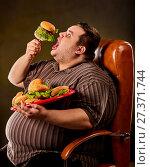 Купить «Fat man eating fast food hamberger. Breakfast for overweight person.», фото № 27371744, снято 24 марта 2017 г. (c) Gennadiy Poznyakov / Фотобанк Лори