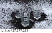 Купить «Empty glasses of vodka standing on the wooden table covered with snow», видеоролик № 27377288, снято 10 января 2018 г. (c) Георгий Дзюра / Фотобанк Лори
