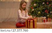Купить «happy girl opening christmas gift at home», видеоролик № 27377760, снято 27 декабря 2017 г. (c) Syda Productions / Фотобанк Лори