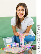 Купить «Woman makes braslets with elastic», фото № 27377988, снято 18 июля 2019 г. (c) Яков Филимонов / Фотобанк Лори