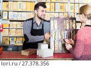 Купить «Seller offering door hinges to female», фото № 27378356, снято 5 апреля 2017 г. (c) Яков Филимонов / Фотобанк Лори