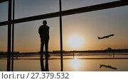 Купить «Silhouette of a tourist guy watching the take-off of the plane standing at the airport window at sunset in the evening. Travel concept, people in the airport.», видеоролик № 27379532, снято 8 января 2018 г. (c) Mikhail Davidovich / Фотобанк Лори