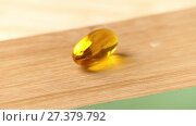 Купить «capsule with fish oil lies on a wooden table», видеоролик № 27379792, снято 26 ноября 2017 г. (c) BestPhotoStudio / Фотобанк Лори