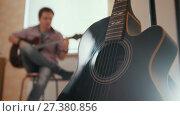 Купить «Young attractive guy musician composes music on the guitar and plays, other musical instrument in the foreground, blurred», видеоролик № 27380856, снято 23 сентября 2018 г. (c) Константин Шишкин / Фотобанк Лори