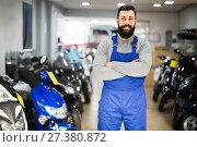Купить «positive man worker displaying various motorcycles in workshop», фото № 27380872, снято 21 сентября 2019 г. (c) Яков Филимонов / Фотобанк Лори