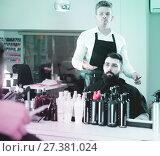 Купить «Young guy stylist demonstrating final haircut to client at hairdressing salon», фото № 27381024, снято 27 января 2017 г. (c) Яков Филимонов / Фотобанк Лори