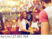Купить «assistant showing customer guitar at music store», фото № 27381764, снято 11 декабря 2014 г. (c) Syda Productions / Фотобанк Лори
