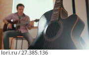 Купить «Young attractive musician composes music on the guitar and plays, other musical instrument in the foreground, blurred concept», видеоролик № 27385136, снято 16 июля 2018 г. (c) Константин Шишкин / Фотобанк Лори