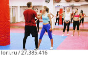 Купить «Young woman is doing self-defence moves with coach in sporty gym.», видеоролик № 27385416, снято 22 октября 2017 г. (c) Яков Филимонов / Фотобанк Лори
