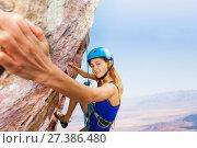 Купить «Sporty young woman in helmet rock climbing», фото № 27386480, снято 28 октября 2017 г. (c) Сергей Новиков / Фотобанк Лори