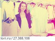 Купить «Young woman shopper choosing new garments», фото № 27388108, снято 19 июня 2017 г. (c) Яков Филимонов / Фотобанк Лори