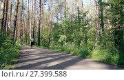 Купить «Красивая девушка бежит по лесной тропе», видеоролик № 27399588, снято 17 сентября 2017 г. (c) Алексей Кокорин / Фотобанк Лори